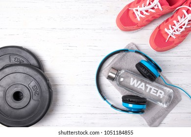 Fitness concept, pink sneakers, bottle of water, weight plates a