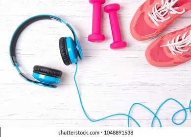 Fitness concept with pink sneakers, dumbbells and blue headphone