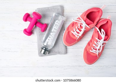 Fitness concept, pink sneakers and dumbbells with bottle of water on wooden background, top view