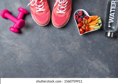Fitness concept, pink sneakers, dumbbells, bottle of water and heart shaped plate with vegetables and berries on a beton background, top view, healthy lifestyle