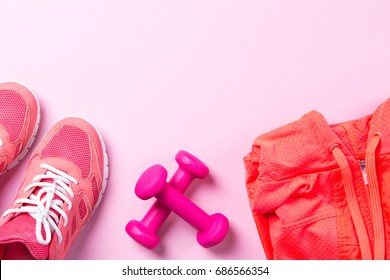 Fitness concept, pink sneakers and dumbbells with sport shirt on pink background, top view with copy space