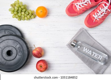 Fitness concept, pink sneakers, weight plates, fruits and bottle