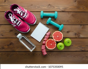 Fitness concept with sneakers dumbbells bottle of water apple and measure tape on wooden table background