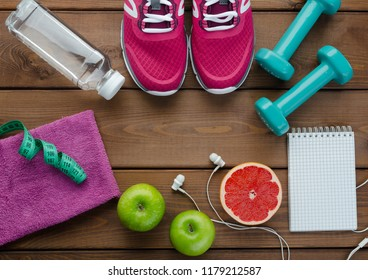 Fitness concept with sneakers dumbbells bottle of water apple pomelo and measure tape on wooden table background      0705