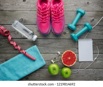 Fitness concept with sneakers dumbbells bottle of water apple pomelo and measure tape on old wooden table background