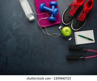 Fitness concept with sneakers dumbbells bottle of water apple and skipping rope on black concrete background