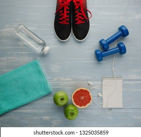 Fitness concept with sneakers dumbbells bottle of water grapefruit apple and pomelo on blue wooden table background