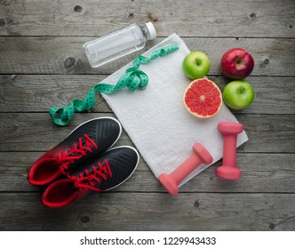 Fitness concept with sneakers dumbbells pomelo bottle of water apple and measure tape on old wooden table background