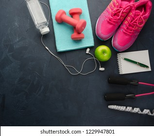 Fitness concept with sneakers dumbbells pomelo bottle of water apple and measure tape on black concrete background