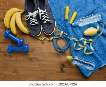 Fitness concept with sneakers dumbbells skipping rope measure tape towel bottle of water pear and bananas on wooden table background