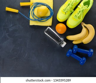 Fitness concept with sneakers dumbbells towel bottle of water bananas oranges and lemons on black concrete background
