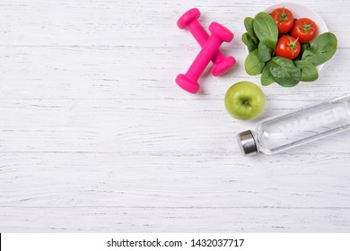 Fitness concept, spinach with tomatoes, bottle with water, green apple and pink dumbbells, diet, top view
