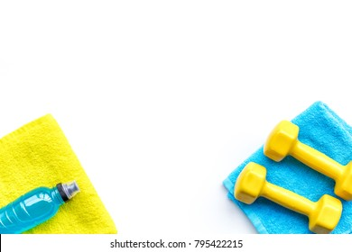Fitness concept. Sport drink, dumbbells, towel on white background top view copy space