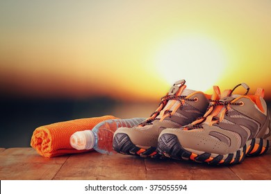 fitness concept with sport footwear, towel and water bottle over wooden table in front of sunset landscape.