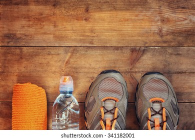 fitness concept with towel and sport footwear over wooden background. top view image