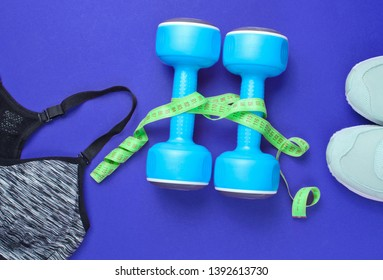 Fitness concept. Weight loss. Sports bra,shoes, dumbbells, ruller on purple background. Top view, flat lay