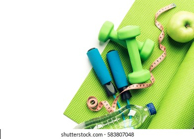 Fitness concept - yoga mat, apple, dumbbells and skipping rope on the white background