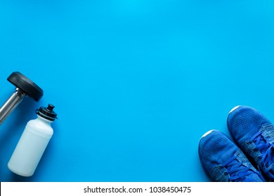 Fitness concepts with sports bottle and gym equipment and running shoes on blue background