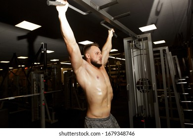 Fitness confidentt man warming up in gym and pulling up on the bar