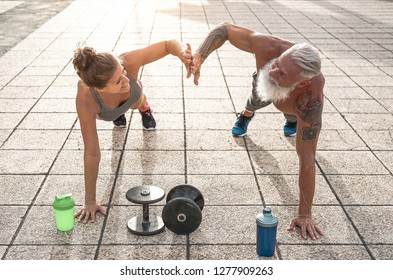 Fitness couple doing push ups exercise outdoor - Happy athletes making workout session outside - Concept of people training, fit, empowering and bodybuilding lifestyle