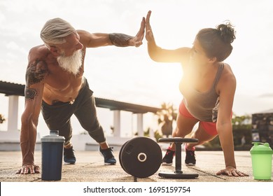 Fitness couple doing push ups exercise outdoor - Happy athletes making workout session at sunset outside - Concept people training and bodybuilding lifestyle
