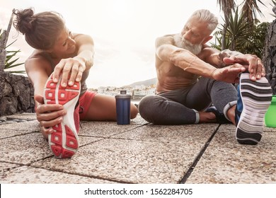 Fitness couple doing stretching exercise outdoor - Happy athletes making workout session at sunset outside - Concept of health mature people training and bodybuilding lifestyle