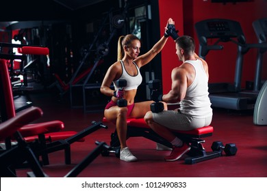 Fitness couple exercising with dumbbell weights in the gym.