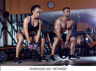 Fitness couple exercising with weight in the gym.