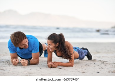 Fitness couple friends talking and laughing while planking on sand, having fun exercising