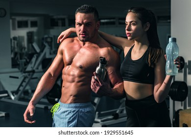 Fitness couple at gym. Personal female trainer helpman working stay hydrated. Sportsman concept. Sport woman. Sporty male with naked torso
