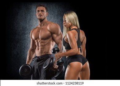 Fitness couple in the gym posing in front of the camera