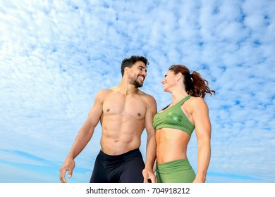 Fitness couple posing on the beach