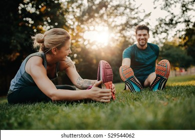 Fitness couple stretching outdoors in park. Young man and woman exercising together in morning. - Shutterstock ID 529544062