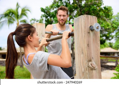 Fitness couple training on chin-up bar together. Woman helped by friend or personal trainer in coaching session supervising exercises on outdoor beach gym.