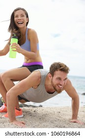 Fitness couple training together having fun. Happy girl laughing sitting on top of personal trainer to make the workout harder.