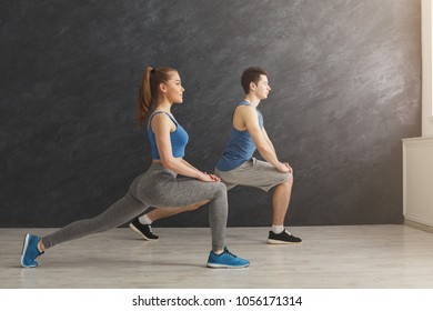 Fitness couple warmup stretching training at gray background indoors. Young man and woman making aerobics exercise at gym, copy space
