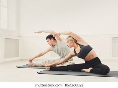 Fitness couple warmup stretching training, sitting on mat indoors. Young man and woman makes aerobics exercise, copy space