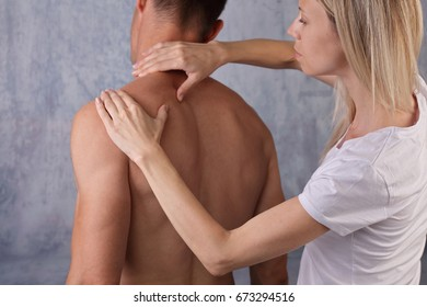 Fitness couple. Woman giving man massage. Back pain, pain relief concept, sport injury