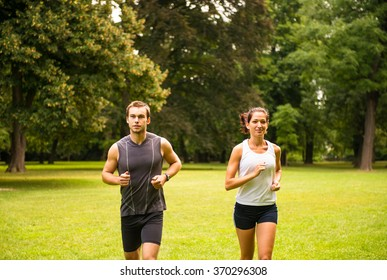 Fitness couple - young man and woman jogging outdoor in nature