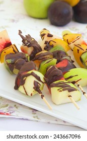 Fitness dessert: fruit salad skewers covered in bitter chocolate. Fruits in the background.