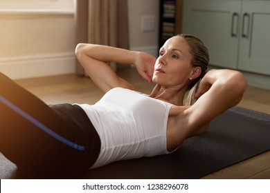 Fitness determined mature woman lying doing crunches at home. Healthy mid woman doing exercises on gym mat. Concentrate middle age lady doing daily exercises lying on the floor in the living room.