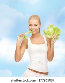 fitness and diet concept - healthy woman biting piece of lettuce