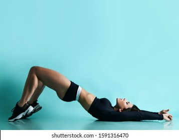 Fitness and diet concept. Young woman with athletic body and perfect buttocks is lying on her back doing fitness exercises lifts workout