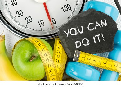 fitness diet motivation background concept apple banana measuring tape and slate on white bathroom scale