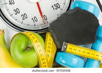 fitness diet motivation background concept apple banana measuring tape and empty slate on white bathroom scale
