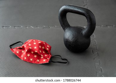 Fitness during a pandemic, fabric face mask and a black kettlebell