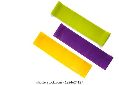 Fitness elastic band, elastic extenders of different colors for sports, isolated on a white background. Fitness trend