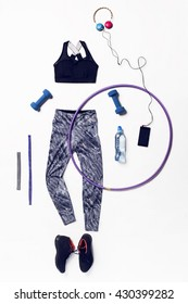 Fitness equipment and clothes, sneakers, water,apple on wooden background