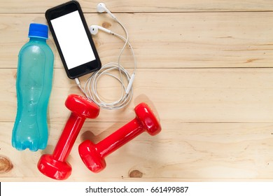 Fitness equipment consisting of dumbbells and Electrolyte Drink on wooden texture and background, vitamin from apple, smartphone for listening to music