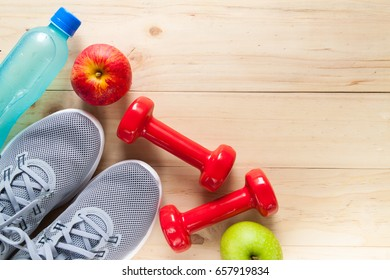 Fitness equipment consisting of dumbbells, training shoes and Electrolyte Drink on wooden texture and background, vitamin from apple
